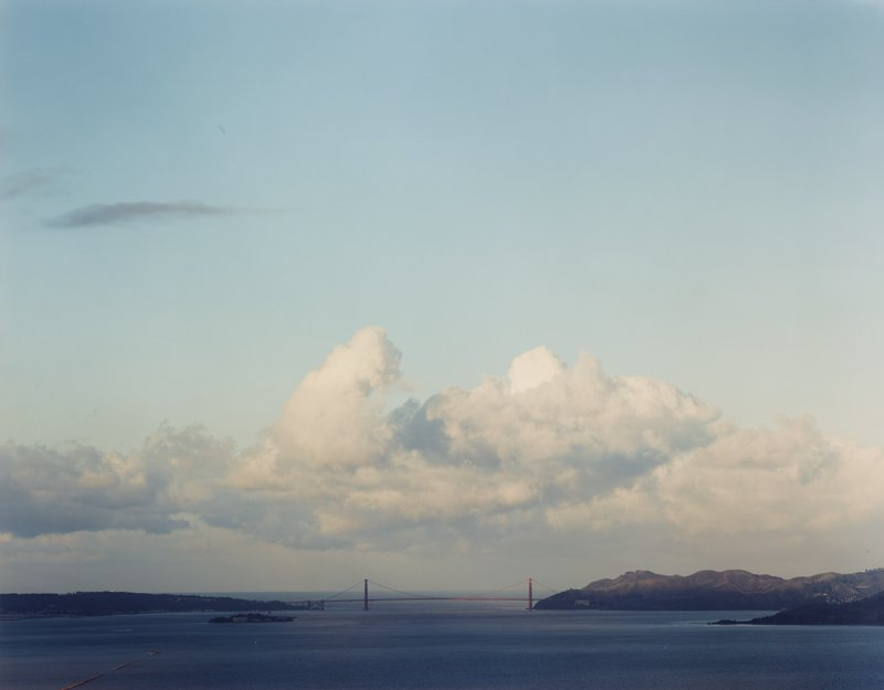 view of suspension bridge (Golden Gate?) across water; island at left; low horizon line; low, large cloud in sky