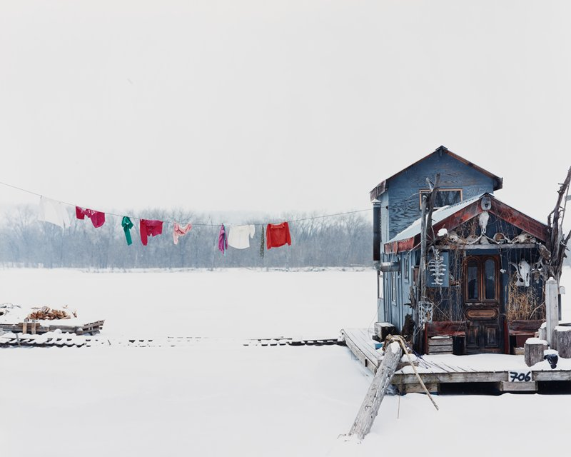 tiny blue houseboat at right on snow-covered lake; clothesline with orange, pink, green, red and white clothing
