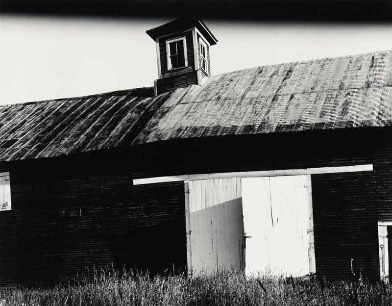 barn with corrugated roof and windowed cupola; white double doors
