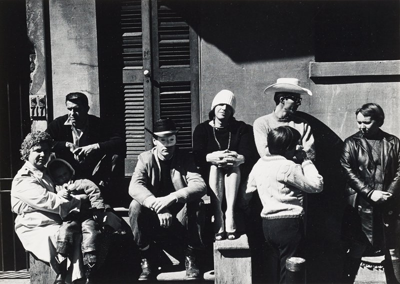people seated on and standing around the stoop of a building; woman at left holding a little boy on her lap; man left of center wearing a cowboy hat and a white mask; man wearing a dress, heels, necklace and a white stocking cap at center