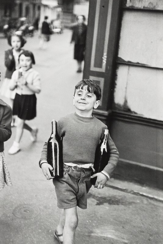 smiling little boy wearing a sweater and shorts, walking down street carrying two bottles of wine; other children and walking figures in background at left