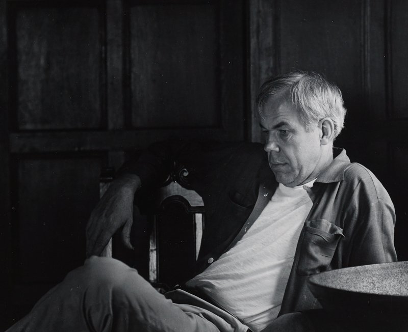 portrait of grey-haired man seated sideways in a chair, slouching, looking down toward left, wearing an open long-sleeved shirt and white t-shirt; wood paneling behind sitter