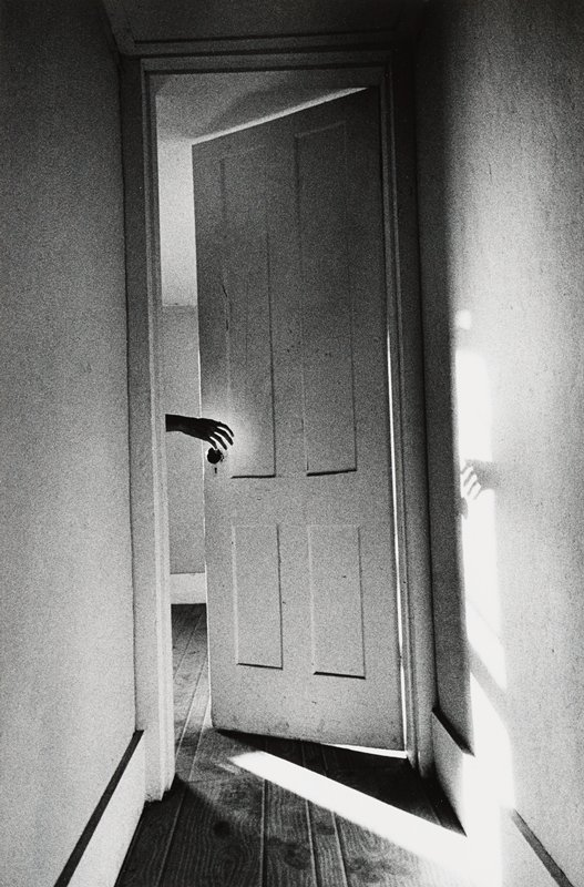 door at end of hallway, open partially, with hand reaching out toward doorknob