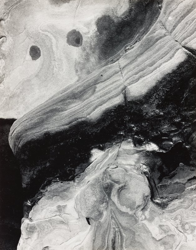 abstract image of natural forms (rock or snow and ice?); striated lines at top; irregular forms at bottom; dark area at center