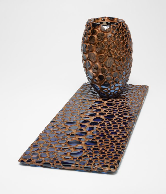 "rectangular glass plate/base with pebbled, deeply incised design; blue surface of ""pebbles"" with dull brown ground; vessel sits on round blue flat element on plate/base; vessel of elongated form, flaring inward at mouth opening; some squared-off planes on sides; vessel has similarly pebbled texture with smoke-colored pebbles"