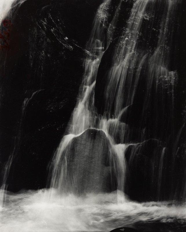 blurry waterfall over dark rocks