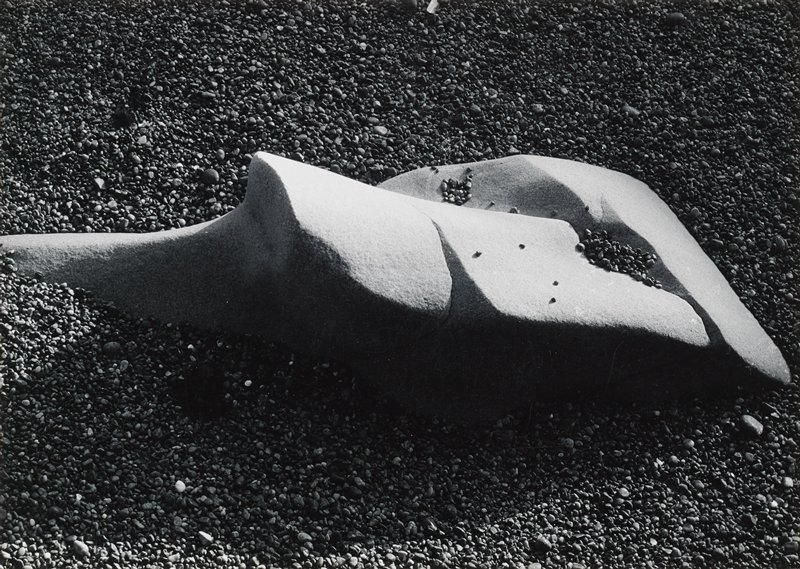 smooth rock with some facets on pebble-covered ground