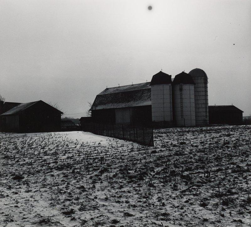 barn, silos and farm field in snow; dark sun in sky