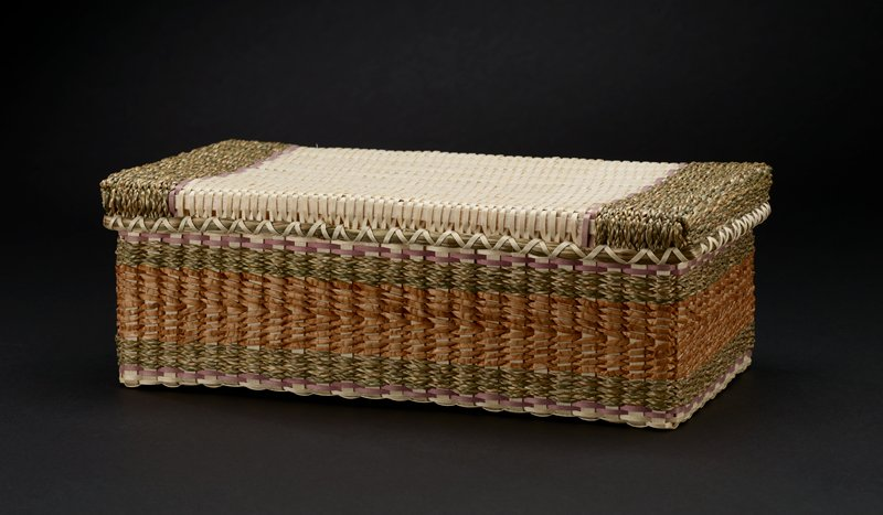 rectangular lidded woven box; cover has light tone at center with two rows of purple stripes bordering wide variegated green-brown stripes at each end; box sides have central tan and brown stripe, flanked by variegated green-brown stripes and thin purple stripes; bottom of box has light tone; loose certification tag with artist's signature inside box