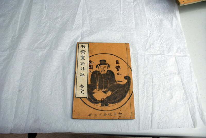 three string-bound volumes of illustrated stories; tan covers with image of artist holding brush; enclosed in blue folding box with ties; box is decorated with grotesque winged figures, dragons, and text vignettes