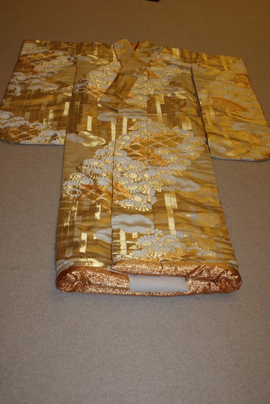 heavy white robe with golden rectangular bars, flowers, clouds; gold lined; padded hem