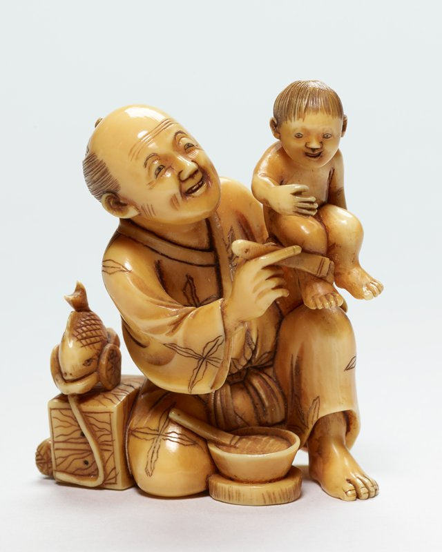 man kneeling on PR knee hoisting a baby over his PL knee with his PL hand; both figures are smiling; man is holding an object against baby's leg