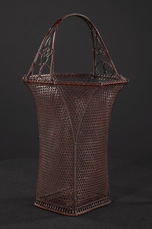 tall, slender deep red/black basket; 4-sided base flairs out into octagonal form near top; open weave with very thin, wiry strands of bamboo that form a star-shaped pattern; woven handle tapers towards center, with looping ornamentation; center lacquered bamboo cylinder with copper lining