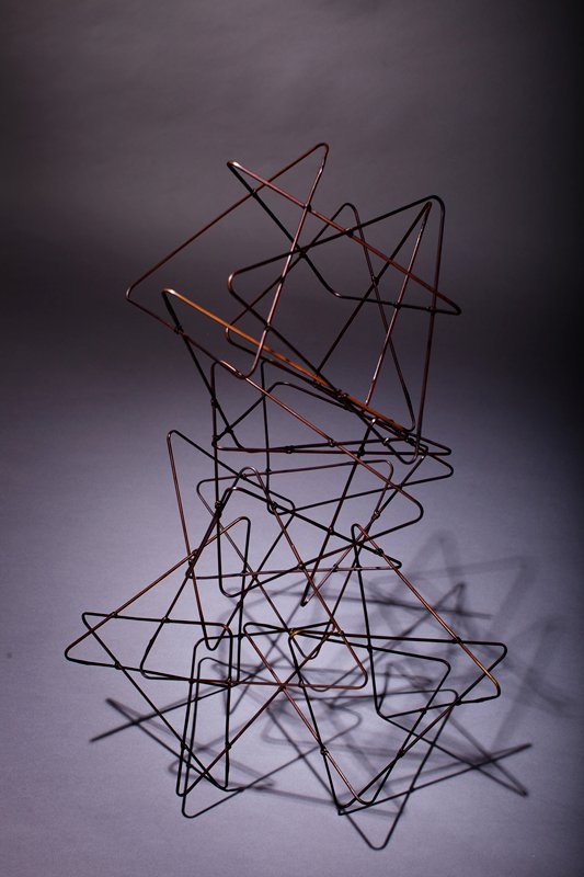 delicate sculpture made of thin triangular strips of bamboo; arranged in a prism shape