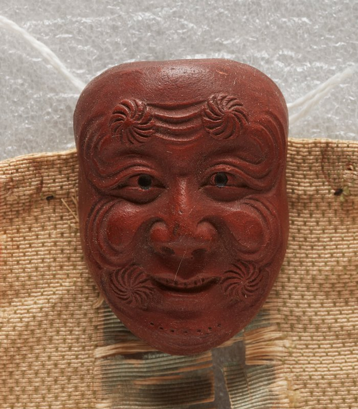 netsuke in the form of a mask; red clay; smiling face with radiating spiraling circles at corners of mouth and two on forehead; curving wrinkles around apples of cheeks and on forehead; 2013.29.1217.1-6 received attached to patterned orange, cream and blue ribbon (ribbon in poor condition--shredded)
