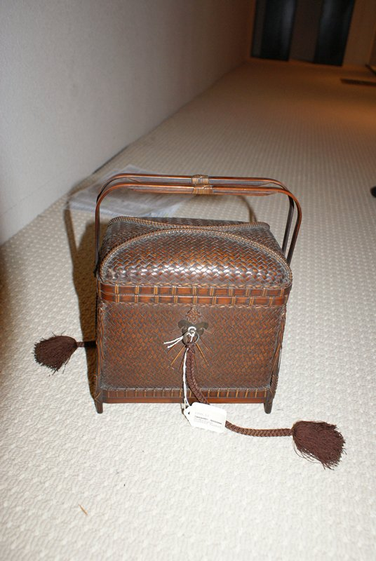 small rectangular basket with removable lid; two handles at side; closed chevron weave; decorative knots with metal hook and bracket on each side for braided brown tassel; decorative weaving on sides; lid has two raised, curved details on top