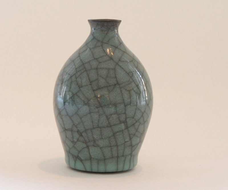 graceful, squat flask with short neck; black clay with crazing celadon over glaze; deep glaze pooling at bottom