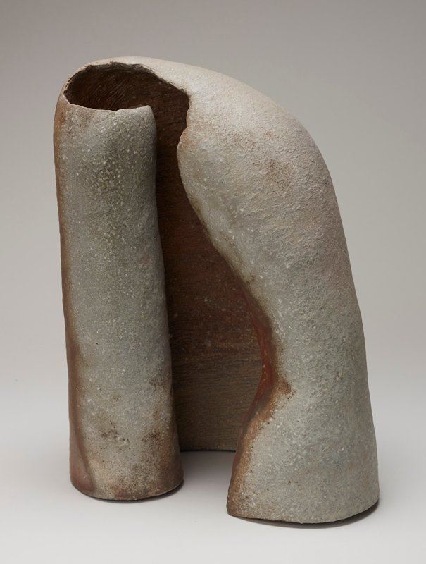 organic form with two inward curling edges; edge on R forms a complete cylinder; incised lines inside back panel; gray color with areas of rust colored red