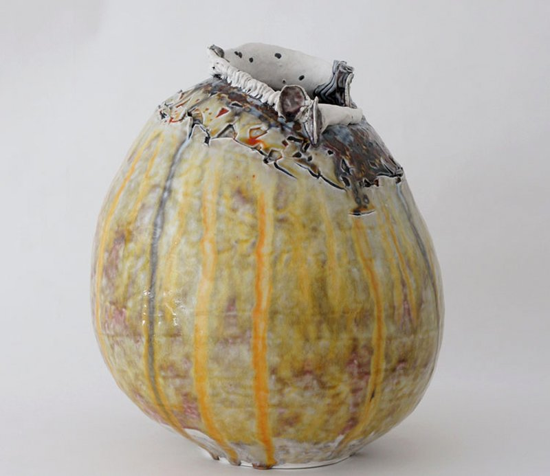hand-built, reduction fire; bits of glass embedded in clay with liquid silver applied on surface; oval shaped ceramic vessel with large opening at top; top lip is folded and crimped; area below lip is intentionally cracked, textured with brown, silver, grey, and orange glaze; vessel is otherwise yellowish tan with yellow, orange, grey streaks; interior glaze is bluish-grey with dark blue and brown streaks