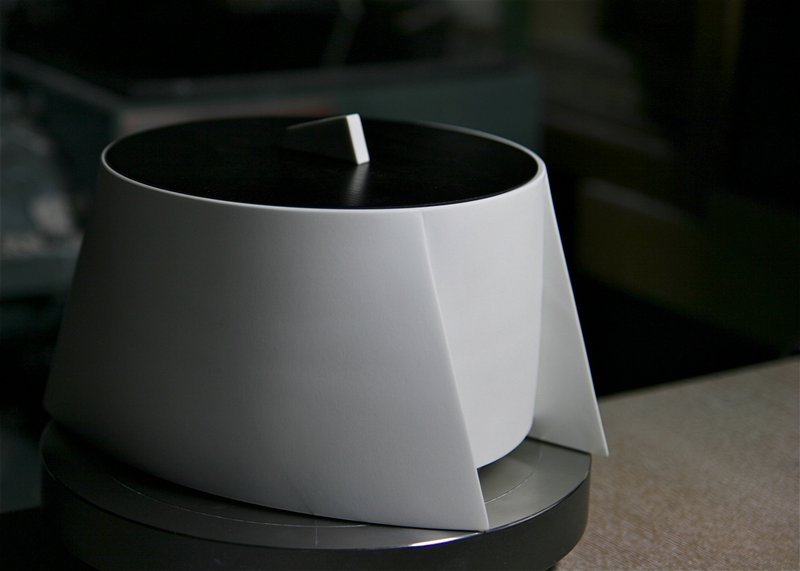 white bowl with high sides; unglazed porcelain; bowl sides taper out on each side forming four pointed, triangular edges; black lacquered cover with triangular white porcelain handle