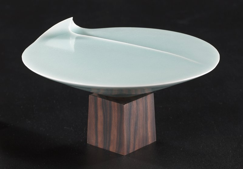 light blue porcelain lily pad with upturned point; elevated vain off-center; mounted to small, dark wooden block