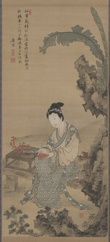 seated woman in robe inscribes red leaf on her lap; woman holds leaf in PL hand and brush in PR hand; to her PR is a small table on a rock platform with inkwell, and red coral holding two calligraphy brushes; behind woman is a large, jagged rock with banana leaves growing toward UR