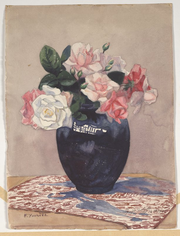 dark blue vase with pink and white roses on a brown and blue cloth on a table