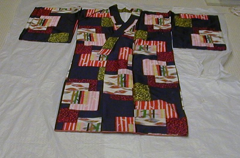 black silk with layered rectangles of varying patterns including red or yellow animal print, leaves on white background, and other abstracted designs with red, yellow, green, and pink