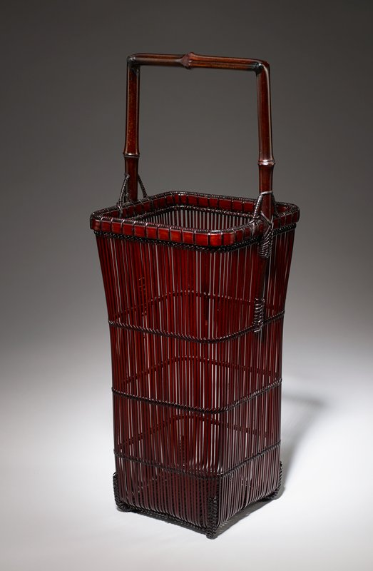 tall, square basket with open weave; minimal horizontal reinforcements; square bamboo handle; no cylinder in box