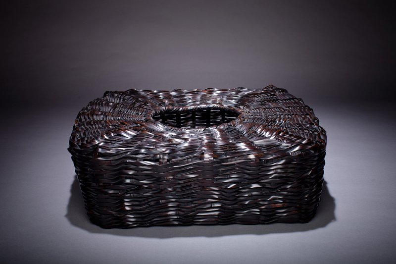 squat, square close-weaved basket; round opening at top; black in color