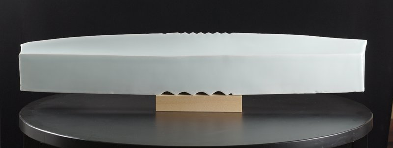 horizontal, blade-shaped form; indented ripples top center, and larger indented ripples bottom center; mounted to light wooden base