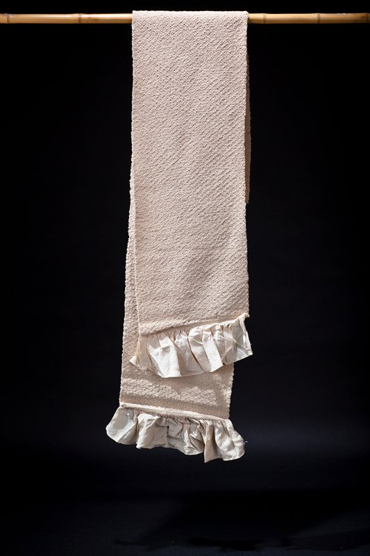 pale peach colored obi with tiny pattern resembling fans made from tightly gathered and tied stitches; ruffles at ends