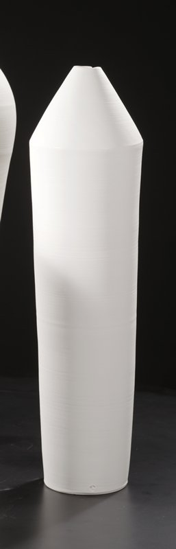 unglazed, white bullet-shaped porcelain vessel; very narrow mouth at top; tapers slightly to base; light orbital lines; a few hash marks upper quadrant