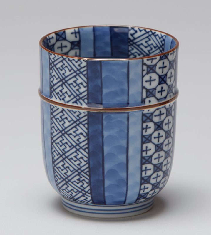 squat teacup with rich alternating floral and linear patterns in blue and white; patterns separated by curving waves of impressed lines; raised thin brown band near top; brown lip; design continued on top inside