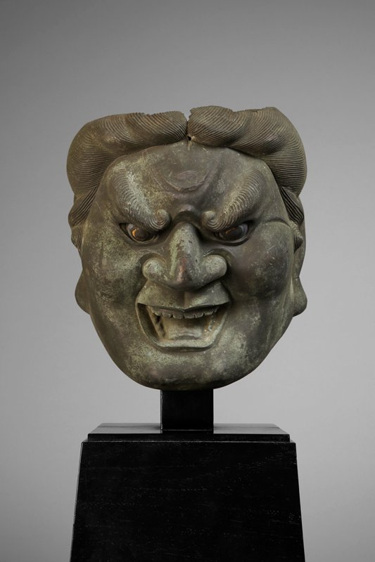 cast bronze head of a deva with gold colored irises; large, downward cast eyes with flecks of gold in irises, hairy, frowning eyebrows; wide open, somewhat smiling sinister mouth; flared nostrils, exaggerated cheek bones; large ears; swirling, yet tamed hair