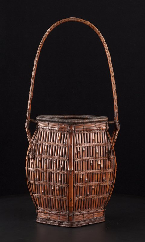 diamond-shaped basket with tall handle covered with many thin vertical strips; vertical weave; decorative weaves along bottom; tall, copper lined cylinder