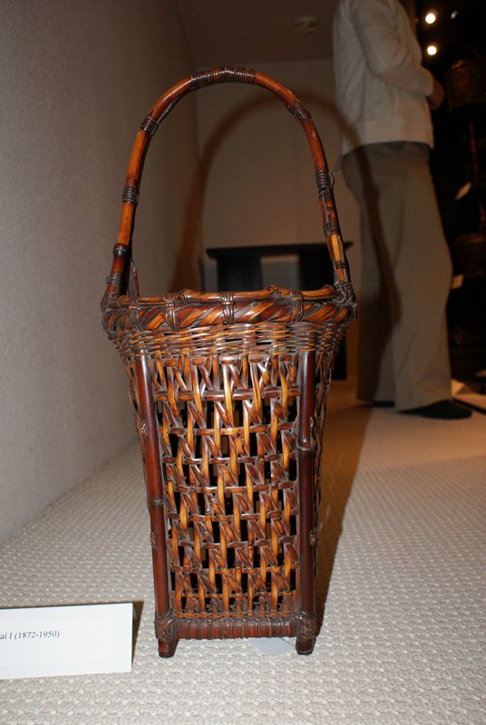 square basket with short feet; flares towards top; round mouth; crisscrossing open weave; copper lined bamboo cylinder