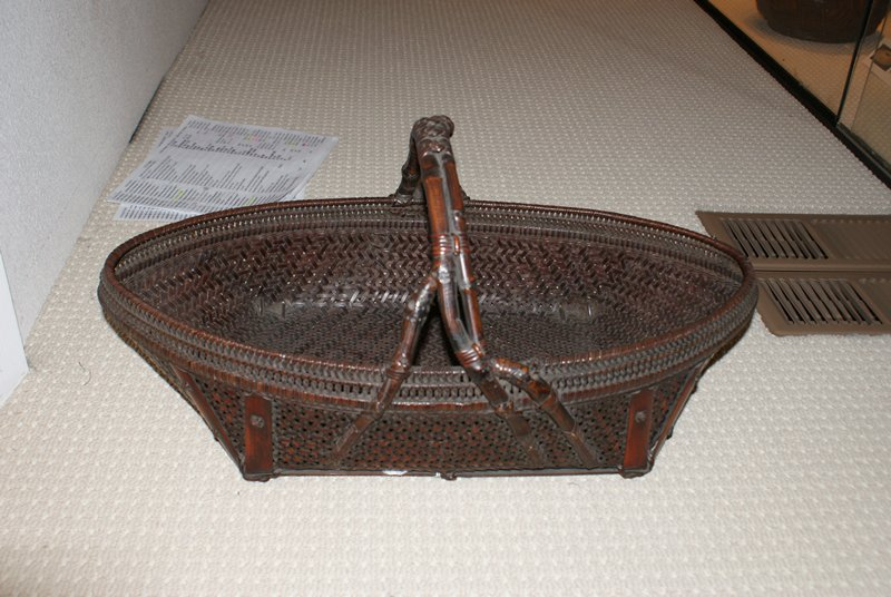 """long, flat, boat-shaped basket with a four-cornered bottom; closely woven, chevron-patterned weave on sides; two bands at top of closely woven, twisted narrow strips; two wide strips with rosette-shaped knots at edges that form """"feet"""" on base; low handle formed from irregularly shaped branches, woven with decorative knots at sides, and three rosettes at top; low, oblong copper tray insert"""