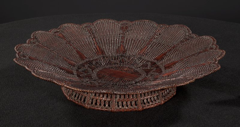 low, flower shaped basket; petals close weave; open weaving with decorative patterns at center; slightly elevated base