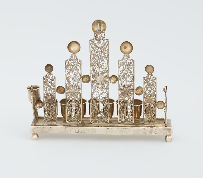 Polish silver Chanukah lamp; Art Nouveau style; row of eight candleholders at front with servant light alongside on PL