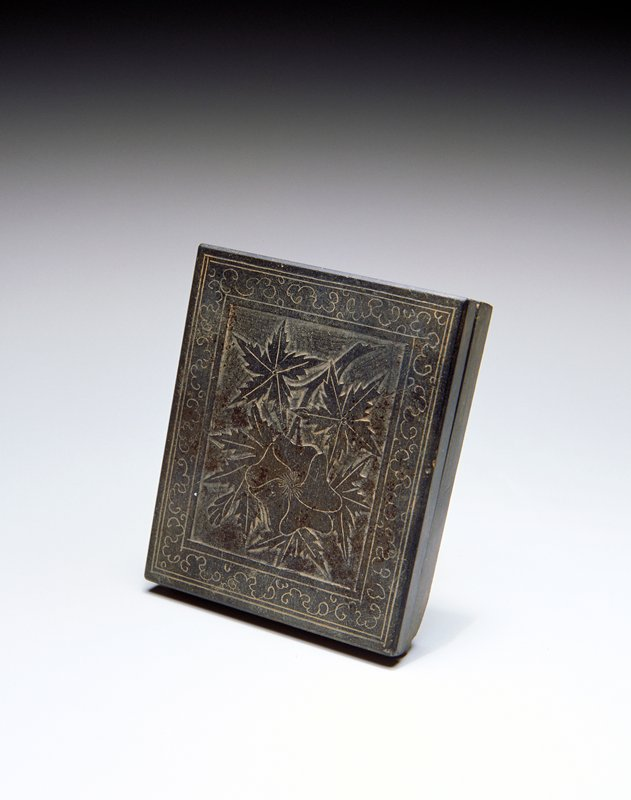 slightly irregular rectangular shape; 2 wells inside base; base concave on bottom; cover decorated with lightly incised flower and star shaped leaves surrounded by a scrolling border