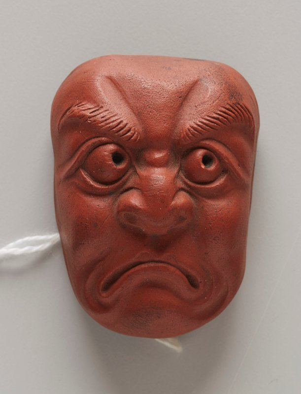 netsuke in the form of a mask; red clay; frowning face with large eyes looking upward toward PL; wide, flat nose; thick eyebrows; wrinkles around mouth