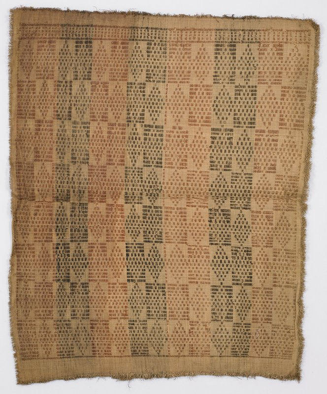 Tan cloth decorated with diamonds and rectangles in light and dark brown; ravelling edges create fringe