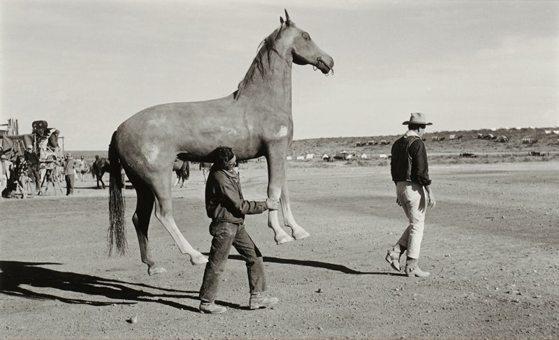man wearing cowboy hat, dark shirt, vest, light-colored pants and cowboy boots at right, walking in front of man wearing blue jeans, boots and jacket, carrying a life-sized model of a horse; people and movie camera in middle ground at left; desert landscape