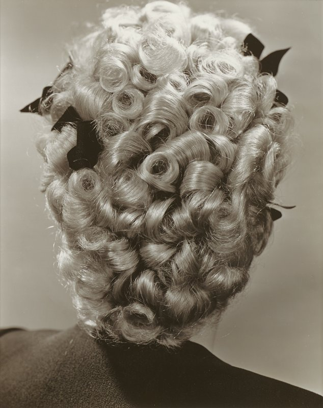 back of woman's head, with hair styled in tight ringlets, with several dark-colored small bows; grey ground