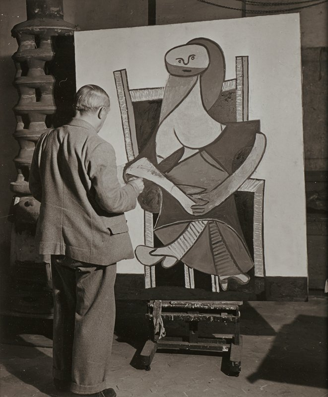 standing man seen from back wearing medium-toned suit, painting an abstract portrait of a seated figure
