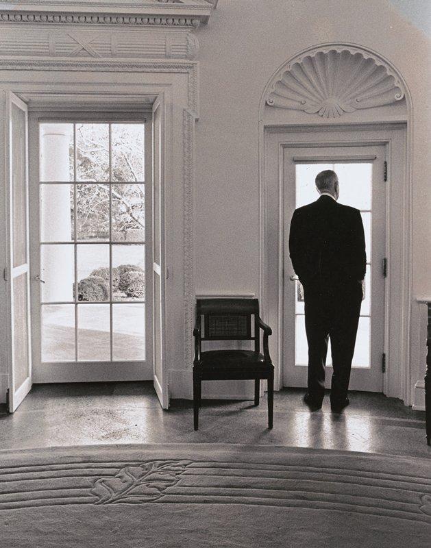 standing man wearing dark suit, seen from back, looking out of glass door in the Oval Office; another door to left, with chair between doorways