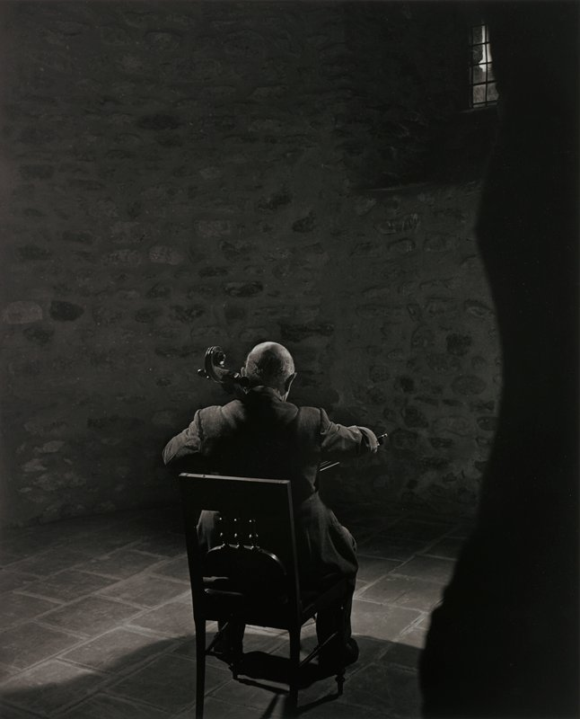 man seen from back, seated in a side chair with three spindles on backrest, playing the cello; window, URC