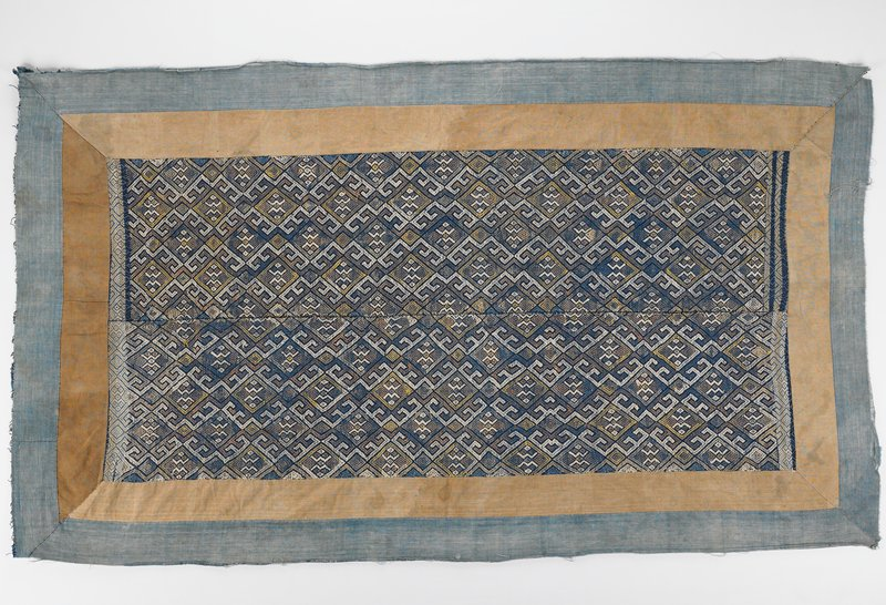 2 woven panels sewn together; geometric pattern with diamonds in white, tan, blue and yellow; double border of brown surrounded by blue