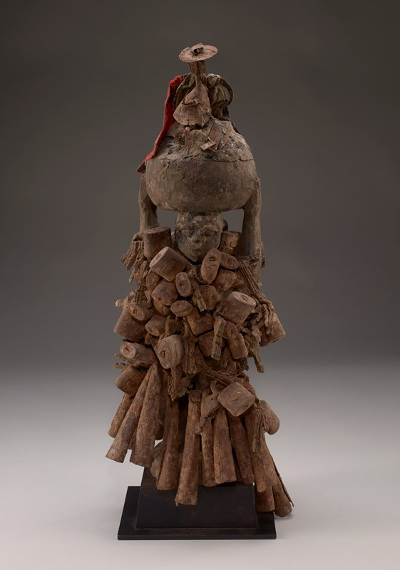 standing female figure with knees bent, holding a large vessel on top of her head; chains and beaded strings surround woman's body, with large cone-shaped beads forming a long skirt and padlocks and keys covering her torso; brown patina overall from soil encrustations and rust; vessel on figure's head has some bits of red, white, black and printed fabrics, metal ornaments and bird feather and/or hair or fur; attached to black mount